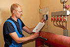 Vvs-montør - Heating and sanitary technician testing and adjusting the heating controller